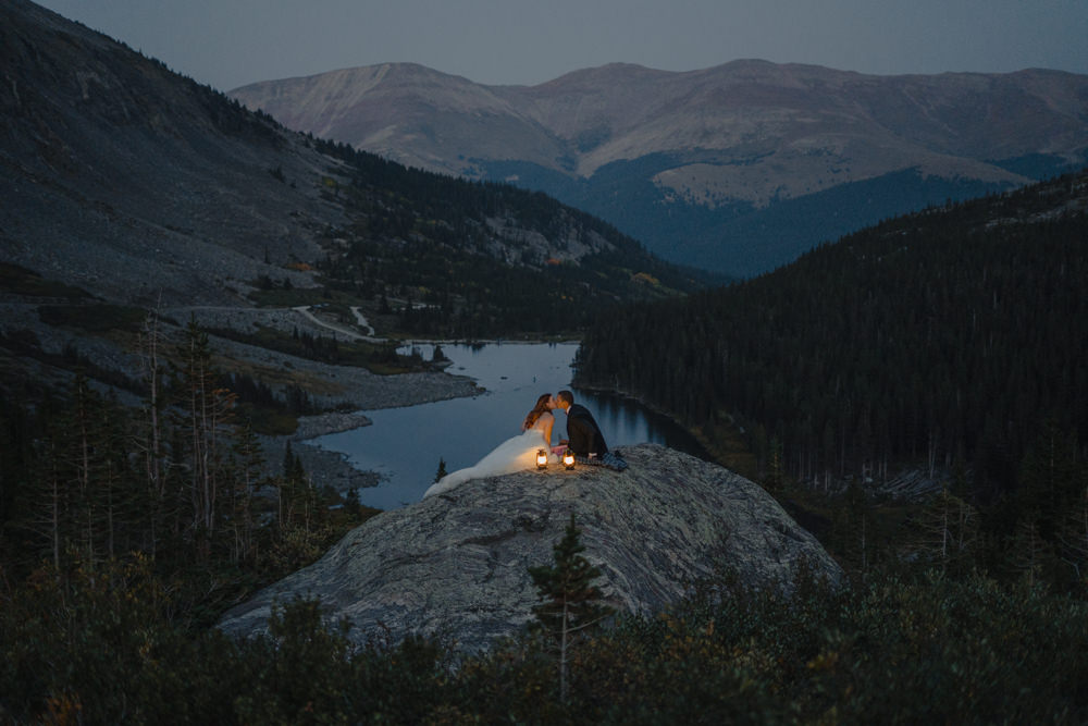 couple celebrating their elopement marriage while looking over mountain range just after sunset
