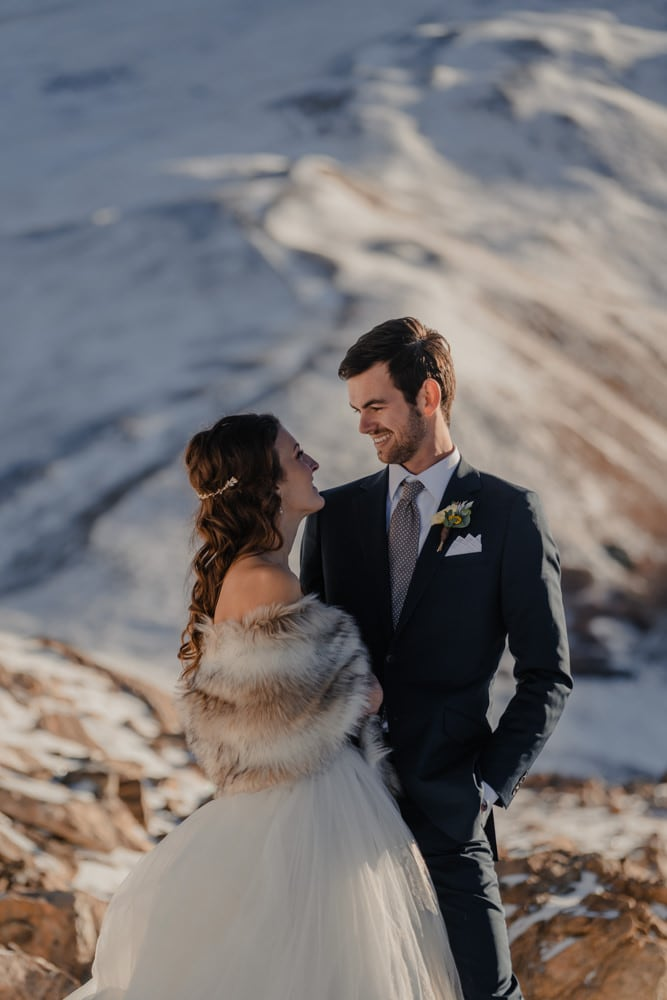 couple posing for a photo during their snow filled elopement