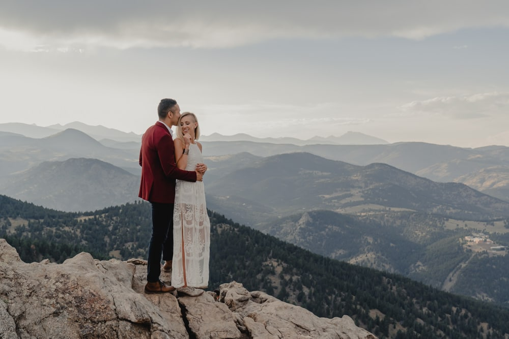 couple celebrating their elopement marriage while looking over mountain range