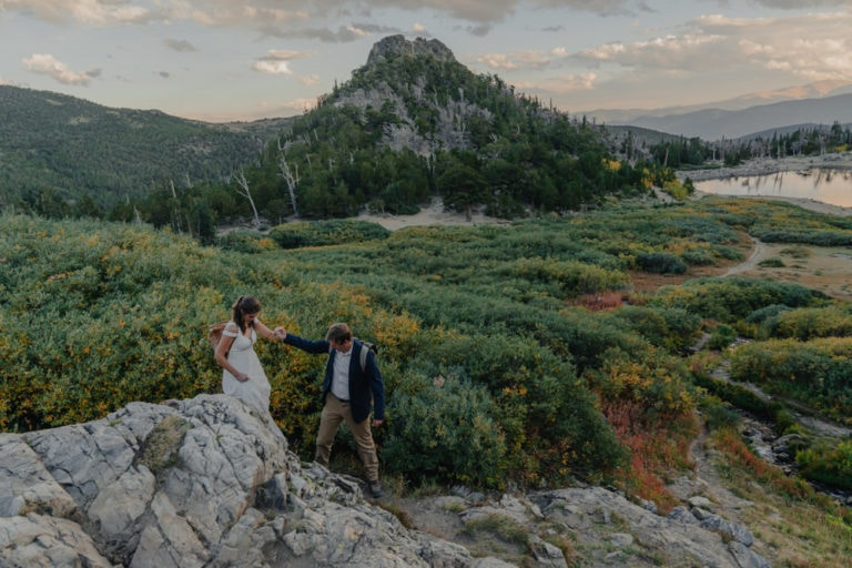 couple hiking down mountain at sunset